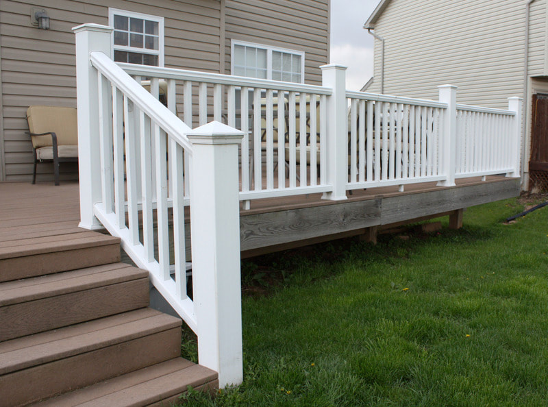 New deck featuring newly painted white railing at a home in Kenosha