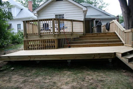 Raised deck with patio and stairs leading up to the home.