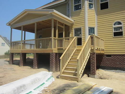 New deck built in Kenosha County. Yellow home with a raised deck.