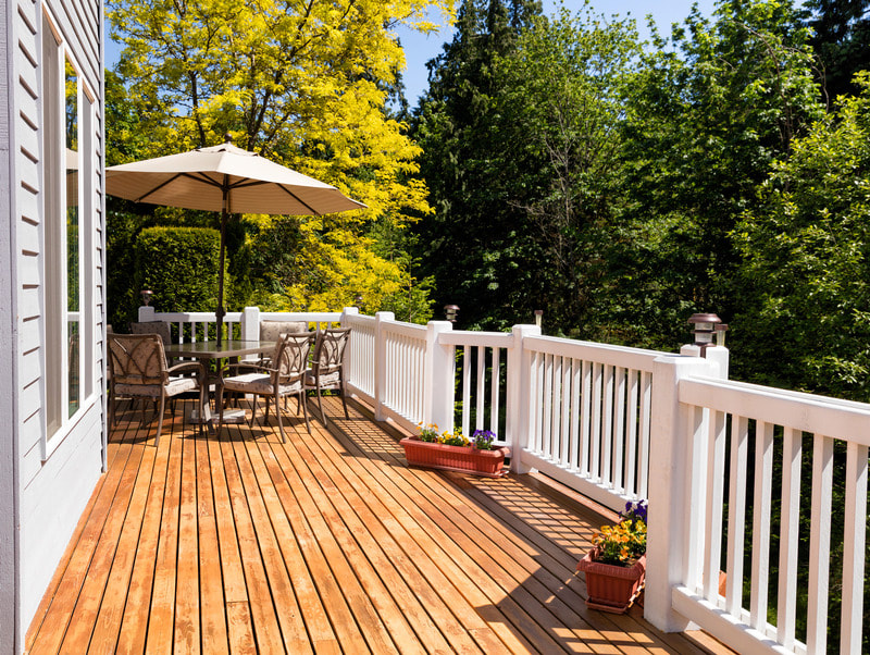 Raised two story deck with white railing and brown wood flooring